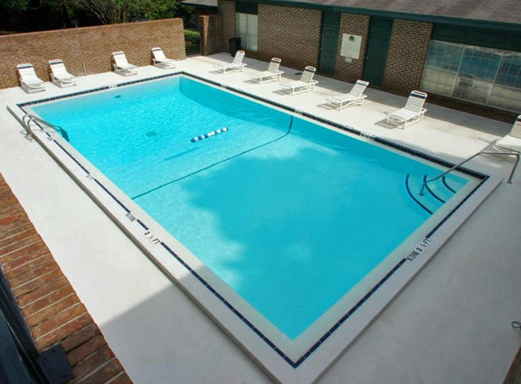 Swimming Pool with lounge chairs behind clubhouse at Aspen Run II