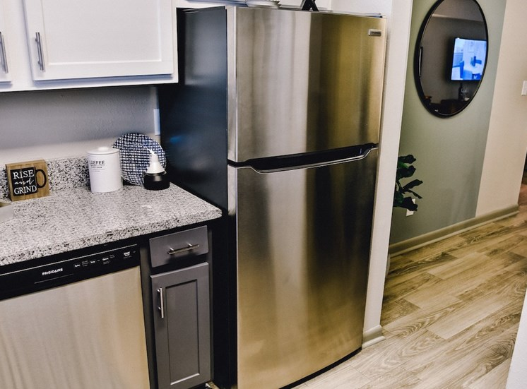 stainless steel dishwasher and fridge and hardwood-inspired floors at The Jameson Apartments, Alabama