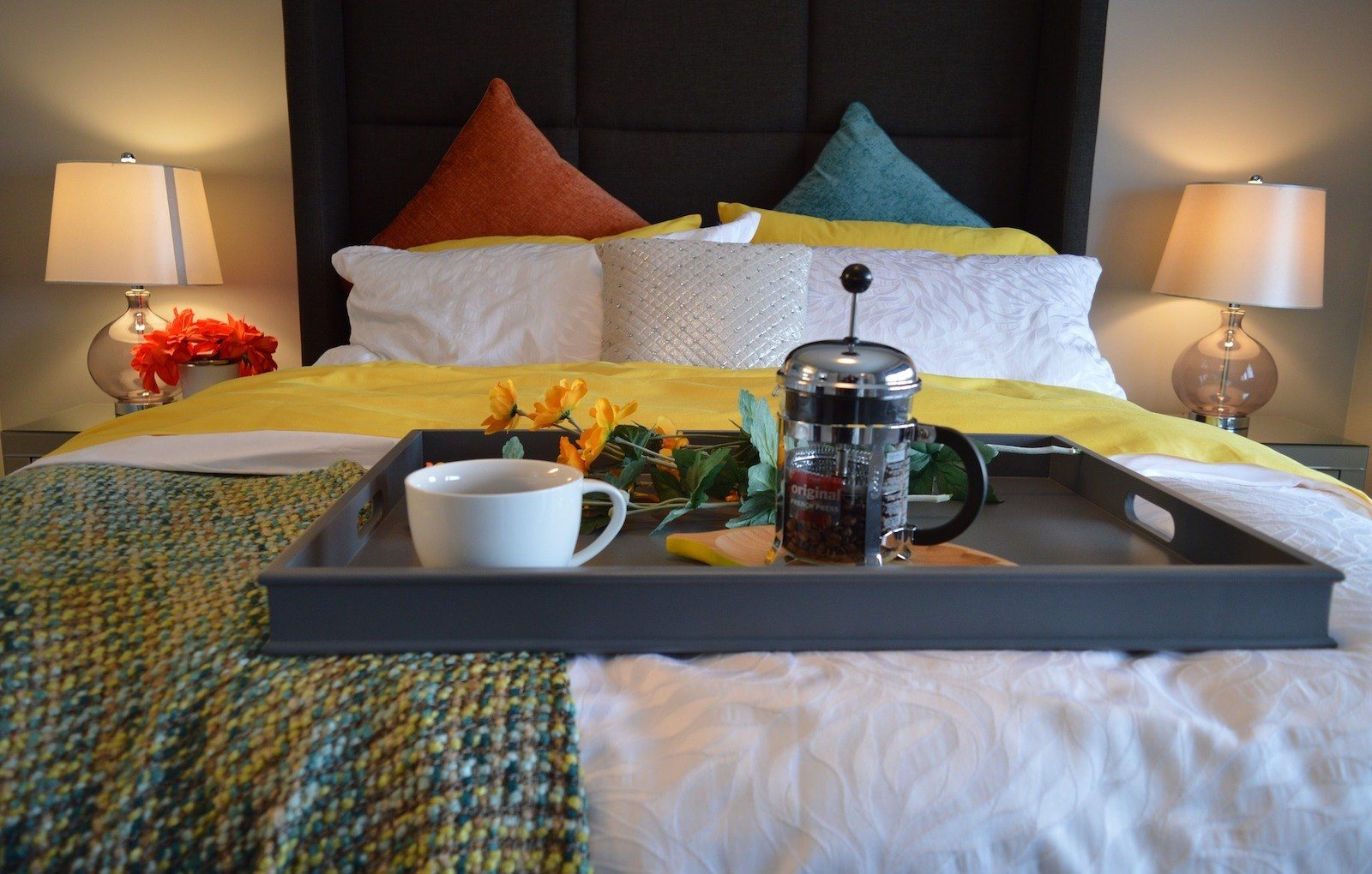 bed with accent pillows and breakfast tray with coffee