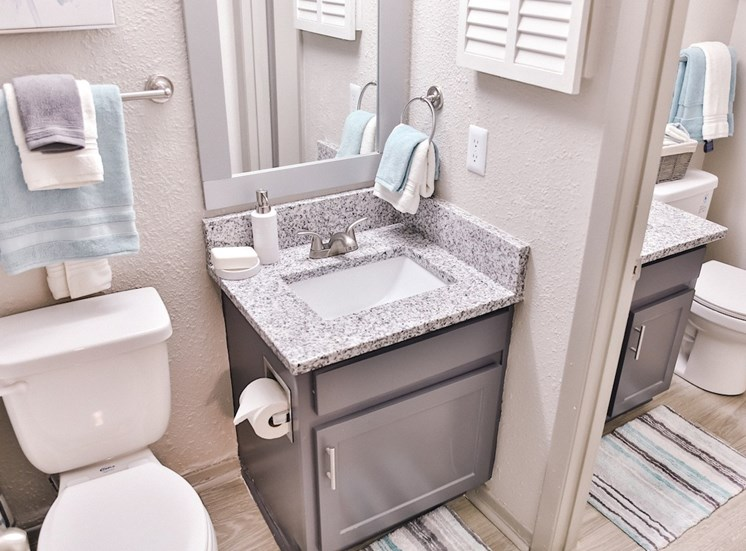 jack and jill bathroom with hardwood-style floors, and granite coutertops