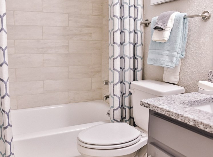 bathroom with granite countertop and tile surround bathtub