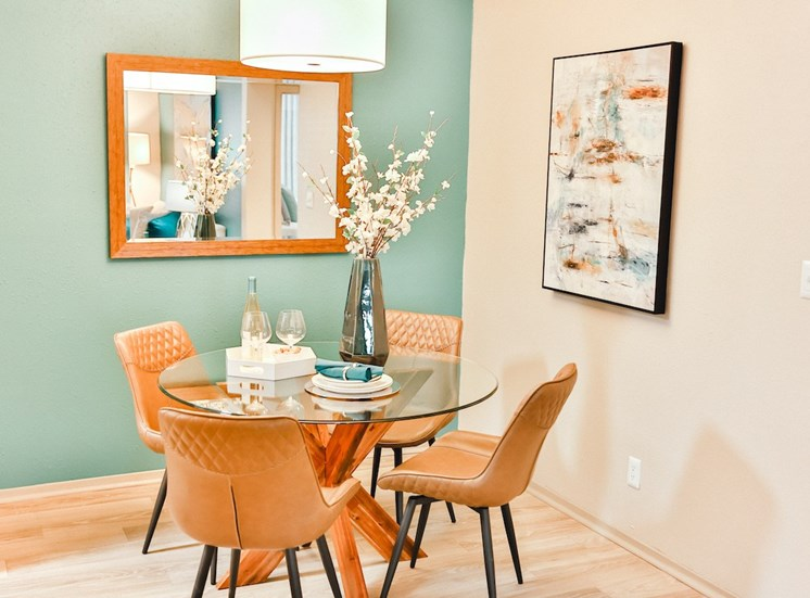 dining room with table, chairs, wall art, and hardwood-inspired floors