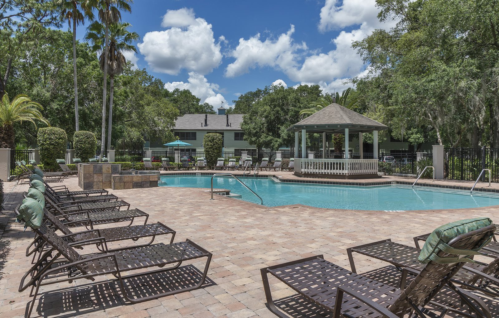swimming pool with massive sundeck, chairs, gazebo, and lush trees at The Retreat at Lakeland Apartments, Lakeland