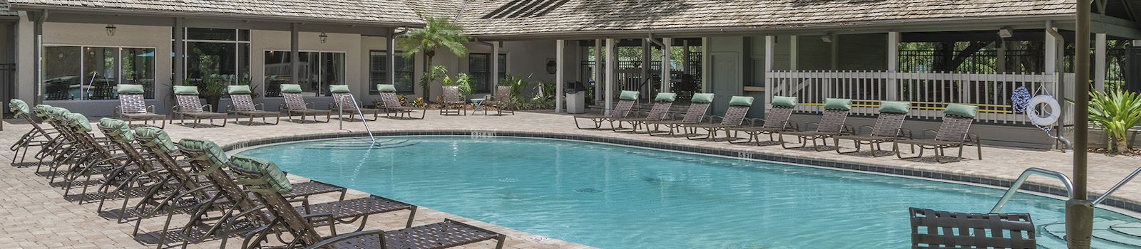large pool with expansive sundeck, many deck chairs, and landscaping at The Retreat at Lakeland Apartments, Lakeland, FL