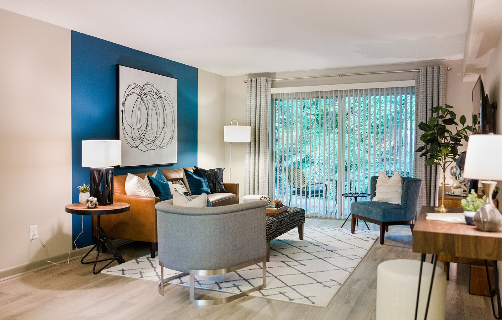 model living room with deck access and accent wall and modern furnishings at The Jameson Apartments, Homewood, 35209
