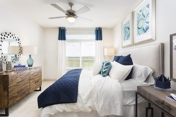 furnished bedroom with ceiling fan and large windows