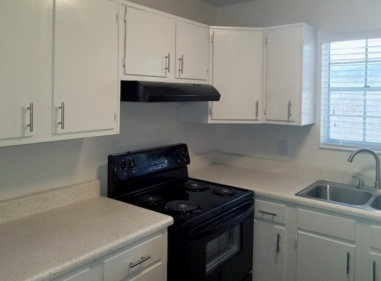 black stove and exhaust hood in kitchen with white cabinets at Apsen Run II