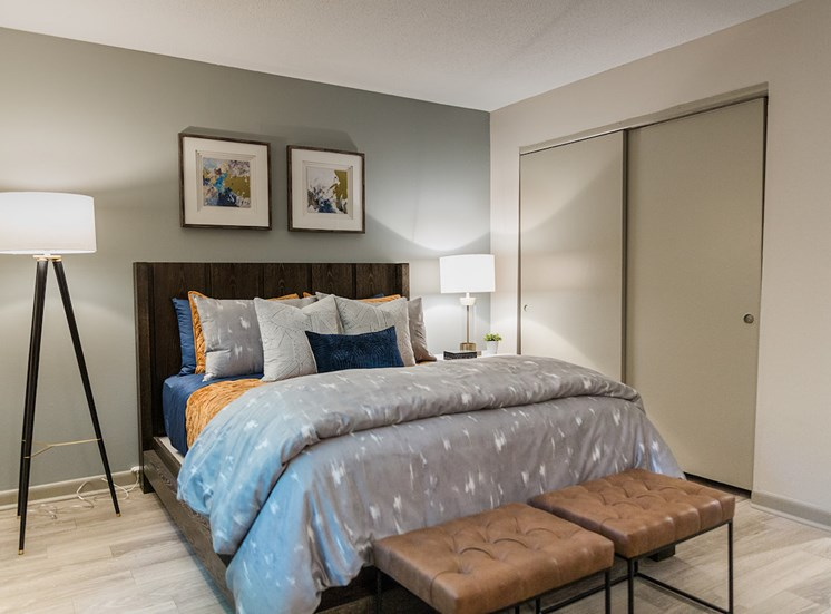 Bedroom with hardwood-style floors, large closet, and model furniture at The Jameson Apartments, Homewood, Alabama