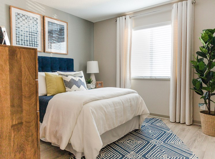 Bedroom with large window and model furnishings at The Jameson Apartments, Homewood, AL