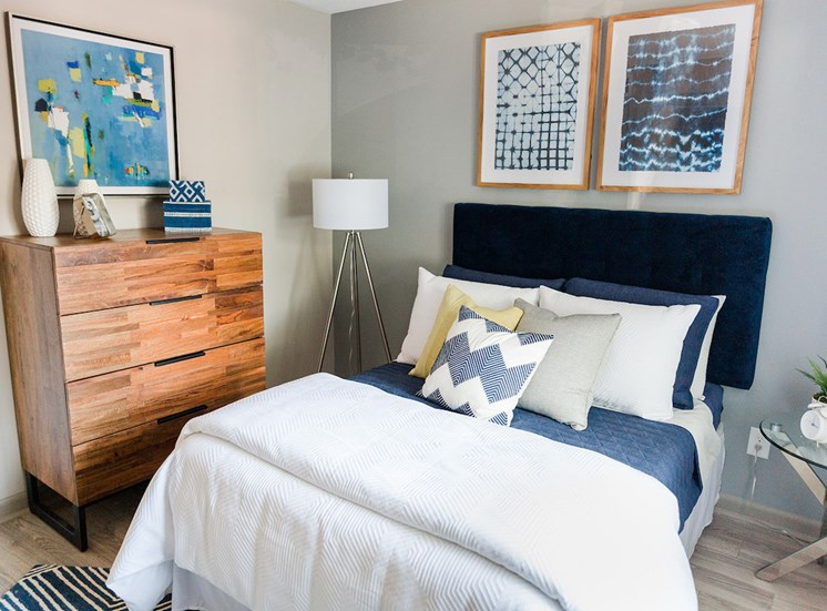 Bedroom with model dresser, lamp, bed, and nightstand at The Jameson Apartments, Homewood, AL, 35209
