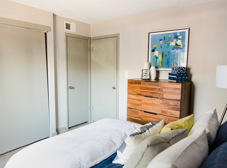 Bedroom with closet and bathroom access and model furniture at The Jameson Apartments, Alabama, 35209