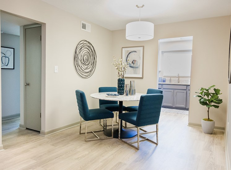 Dining area with hardwood-style floor and model dining set at The Jameson Apartments, Homewood