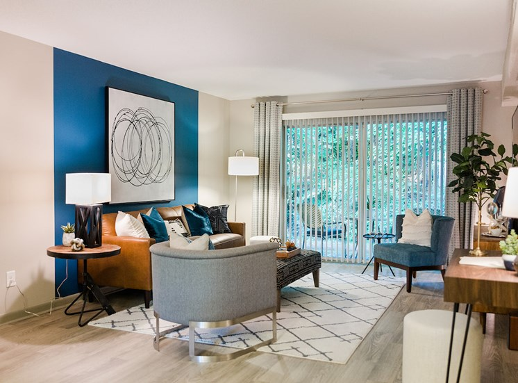 Living room with model furnishings and sliding glass doors to deck at The Jameson Apartments, Alabama