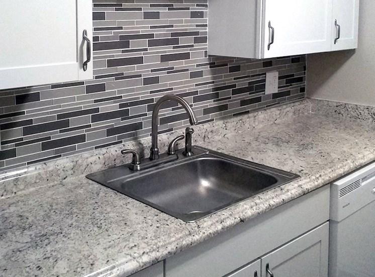 sink with tile backsplash in kitchen at Aspen Run II