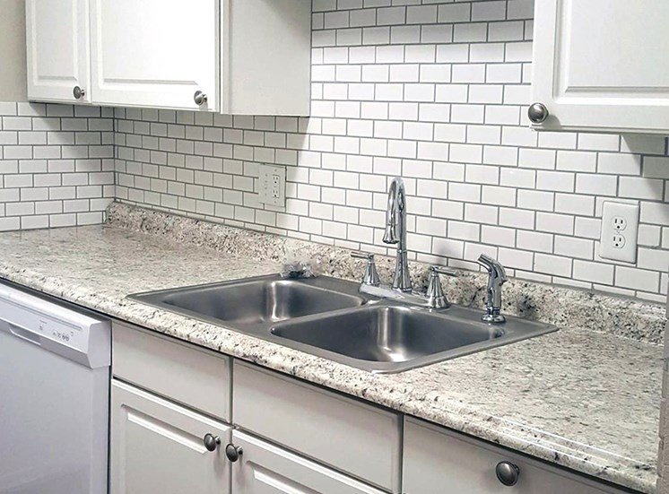Stainless Steel kitchen sink with white subway tile backsplash and white cabinets