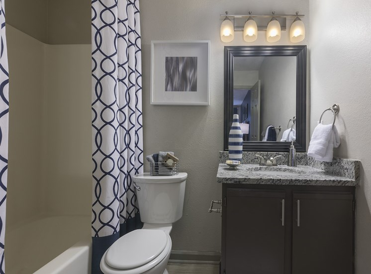 bathroom with granite vanity, tub and shower, and toilet at The Retreat at Lakeland Apartments, Florida, 33809
