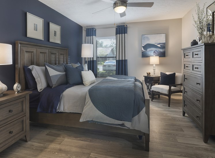 Bedroom with large window, hardwood-style floors, ceiling fan, and accent wall at The Retreat at Lakeland Apartments, Florida