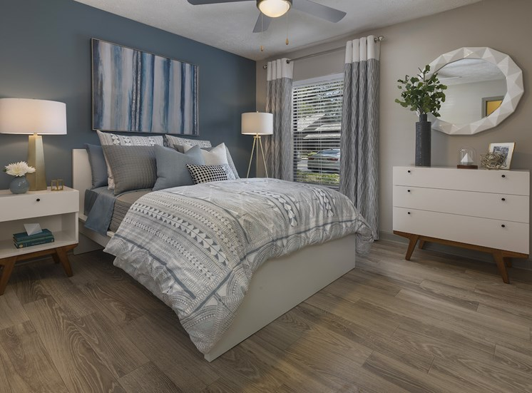Bedroom with accent wall, window, fan, and hardwood-style flooring at The Retreat at Lakeland Apartments, Lakeland, Florida