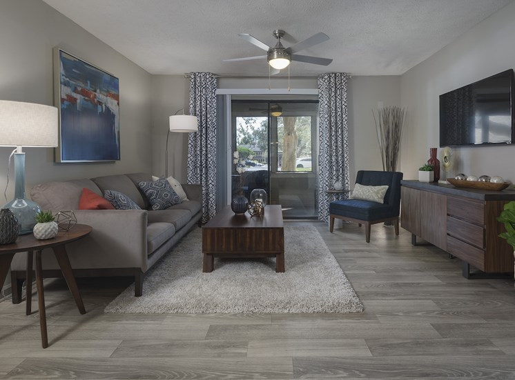 large living room with ceiling fan, hardwood-style floors, and sliding glass doors to deck, at The Retreat at Lakeland Apartments, Florida, 33809