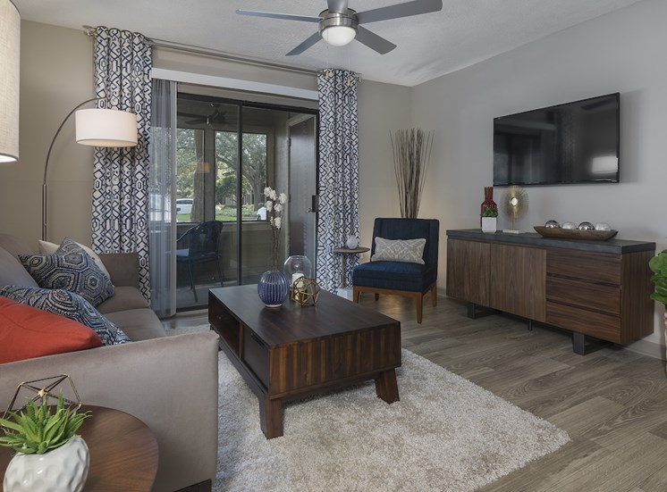 Living room with hardwood-style floors, ceiling fan, and model furnishings at The Retreat at Lakeland Apartments, Florida