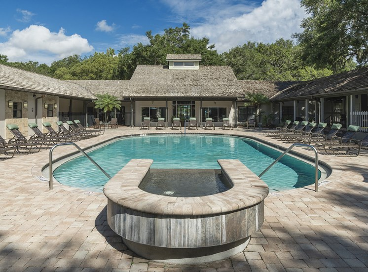 second pool with waterfall and large sundeck with chairs at The Retreat at Lakeland Apartments, Lakeland