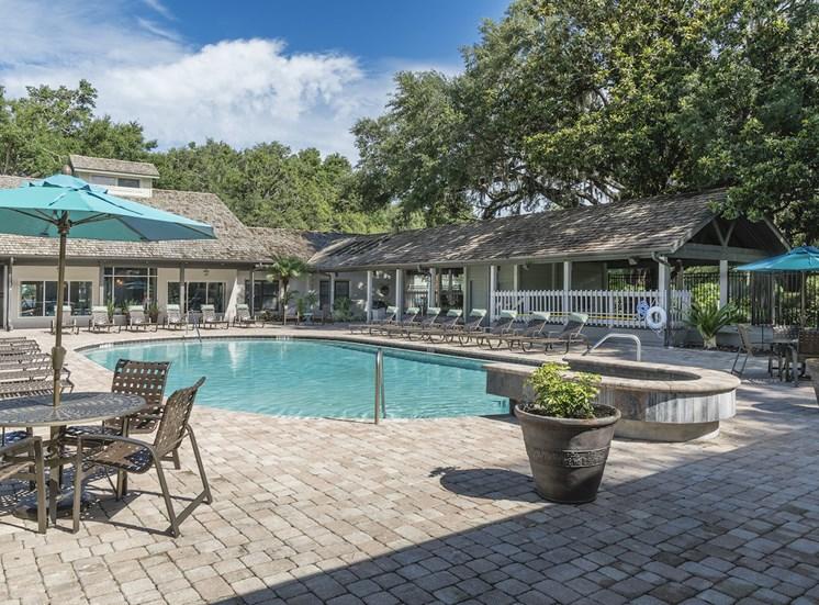 swimming pool with picnic tables and umbrellas and landscaping at The Retreat at Lakeland Apartments, Lakeland, Florida