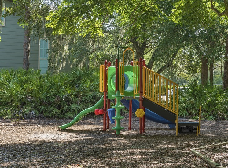 Modern playground equipment surrounded by lush trees at The Retreat at Lakeland Apartments, Lakeland, FL