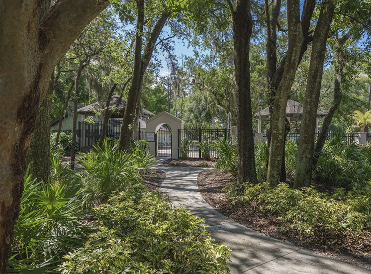well-kept walking path surrounded by trees leading to pool at The Retreat at Lakeland Apartments, Florida, 33809
