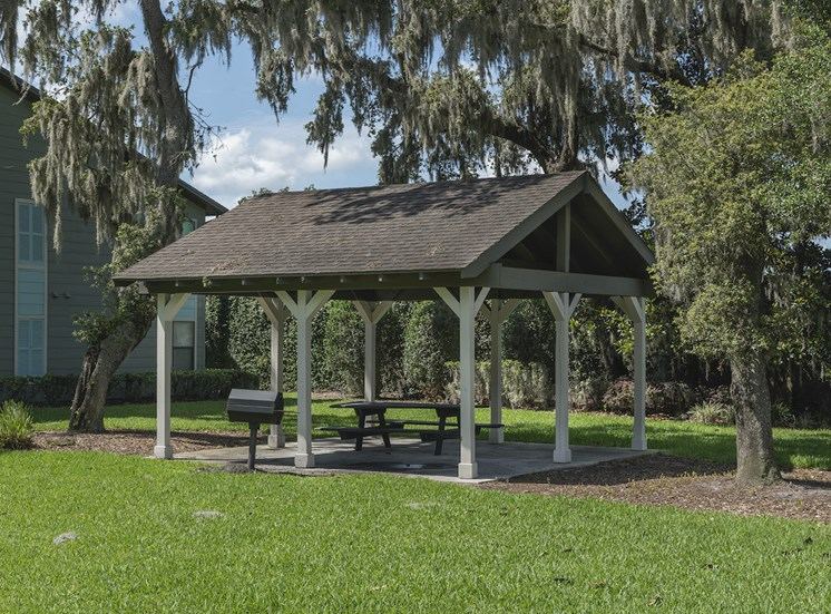 covered picnic area with grill and lush landscaping at The Retreat at Lakeland Apartments, Lakeland