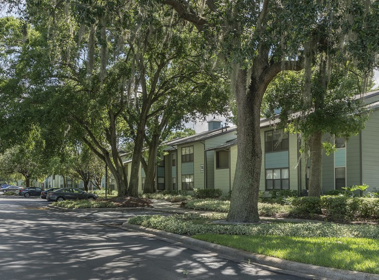 apartment buildings surrounded by large oak trees and plenty of parking at The Retreat at Lakeland Apartments, Lakeland, FL