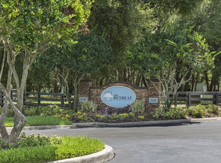 monument sign at entrance with lush landscaping at The Retreat at Lakeland Apartments, Lakeland, FL, 33809