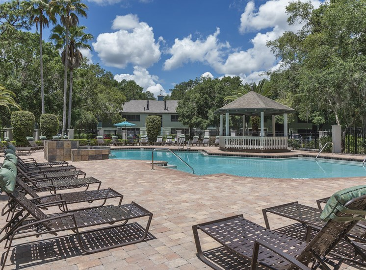 Resort-style pool and sundeck with gazebo and loungers at The Retreat at Lakeland Apartments, Lakeland