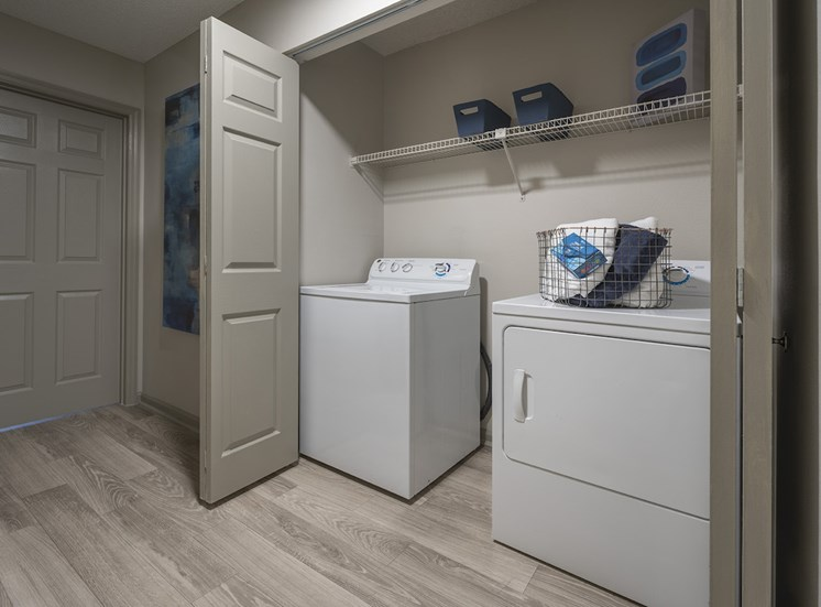in-home laundry room with built-in shelving and rentable washer and dryer