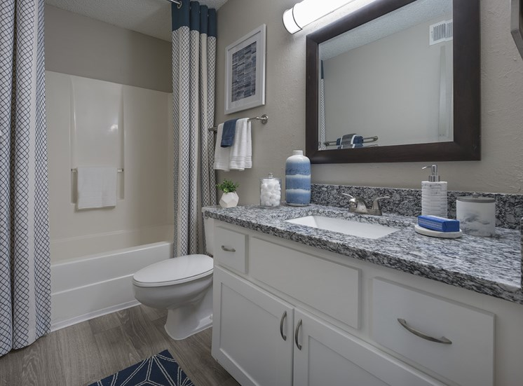 model bathroom with granite countertops, hardwood-style floor, toilet, and tub-shower