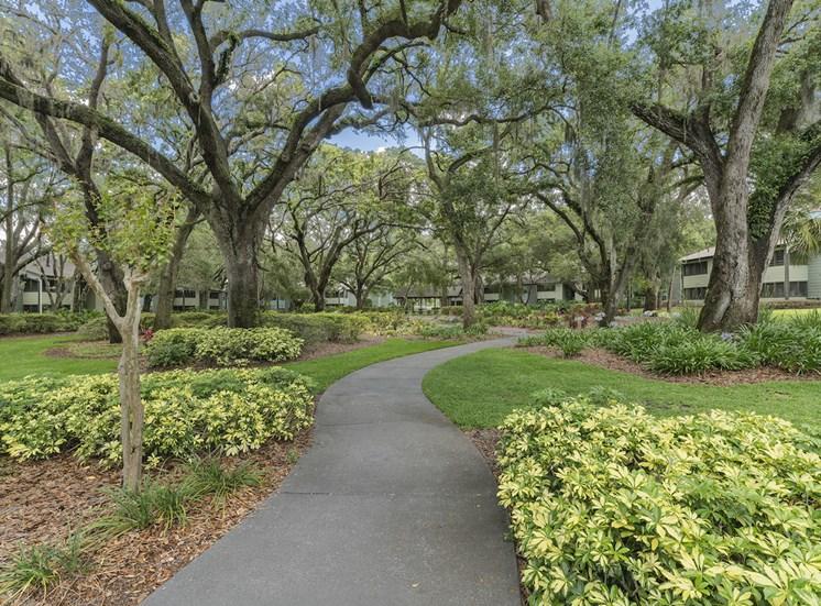 Beautifully landscaped walking path with lush trees and bushes at The Retreat at Lakeland Apartments, Florida
