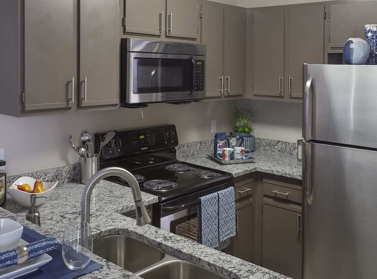 Kitchen with granite countertops, stainless steel appliances, and ample cabinetry at The Retreat at Lakeland Apartments, Lakeland, FL, 33809