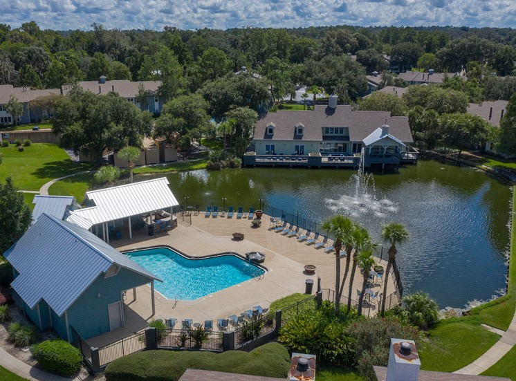 Steeples community with large clubhouse, pool, pond with fountain, and apartment homes