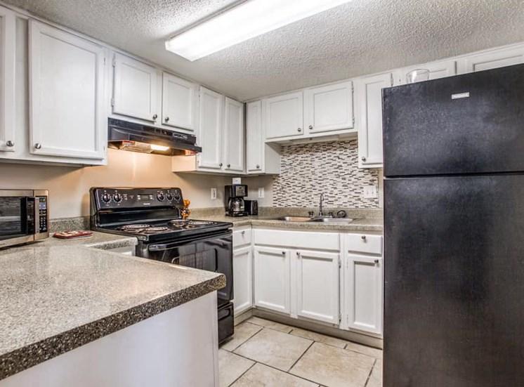 kitchen with black appliances, tile backsplashes, and tile flooring