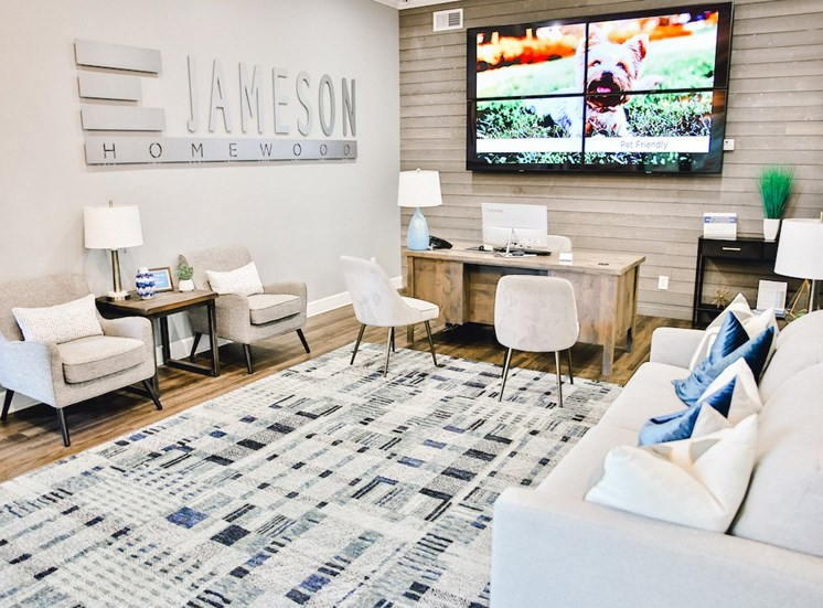 large office with community name on wall, desk, and TV on wall at The Jameson Apartments, Homewood, Alabama