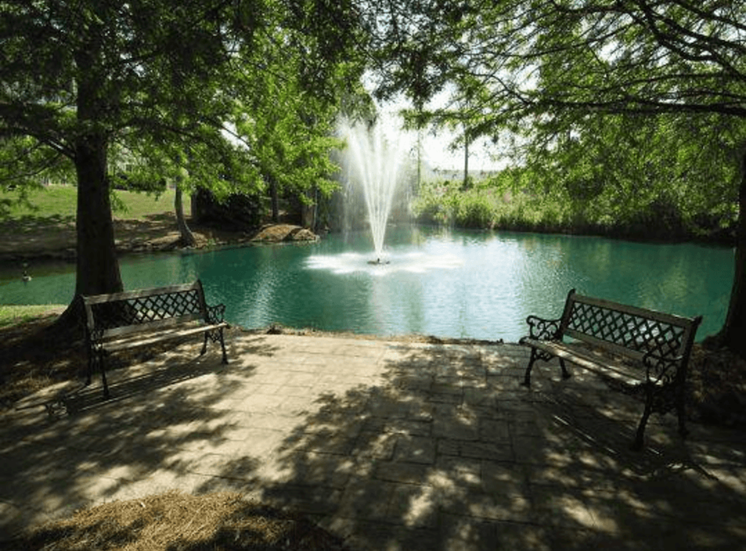 Pond with benches and fountain surrounded by trees at Stillwater at Grandview Cove, Simpsonville, SC, 29680
