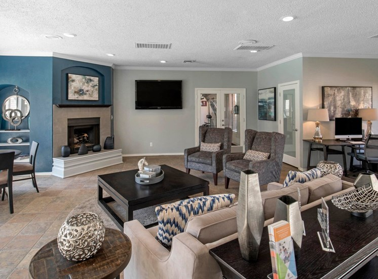 Clubhouse interior, blue accent wall with fireplace, coffee table, two accent chairs, and a cream sofa