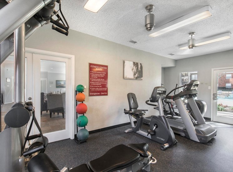 Fitness center and treadmill with medicine workout balls, and a window with a pool view