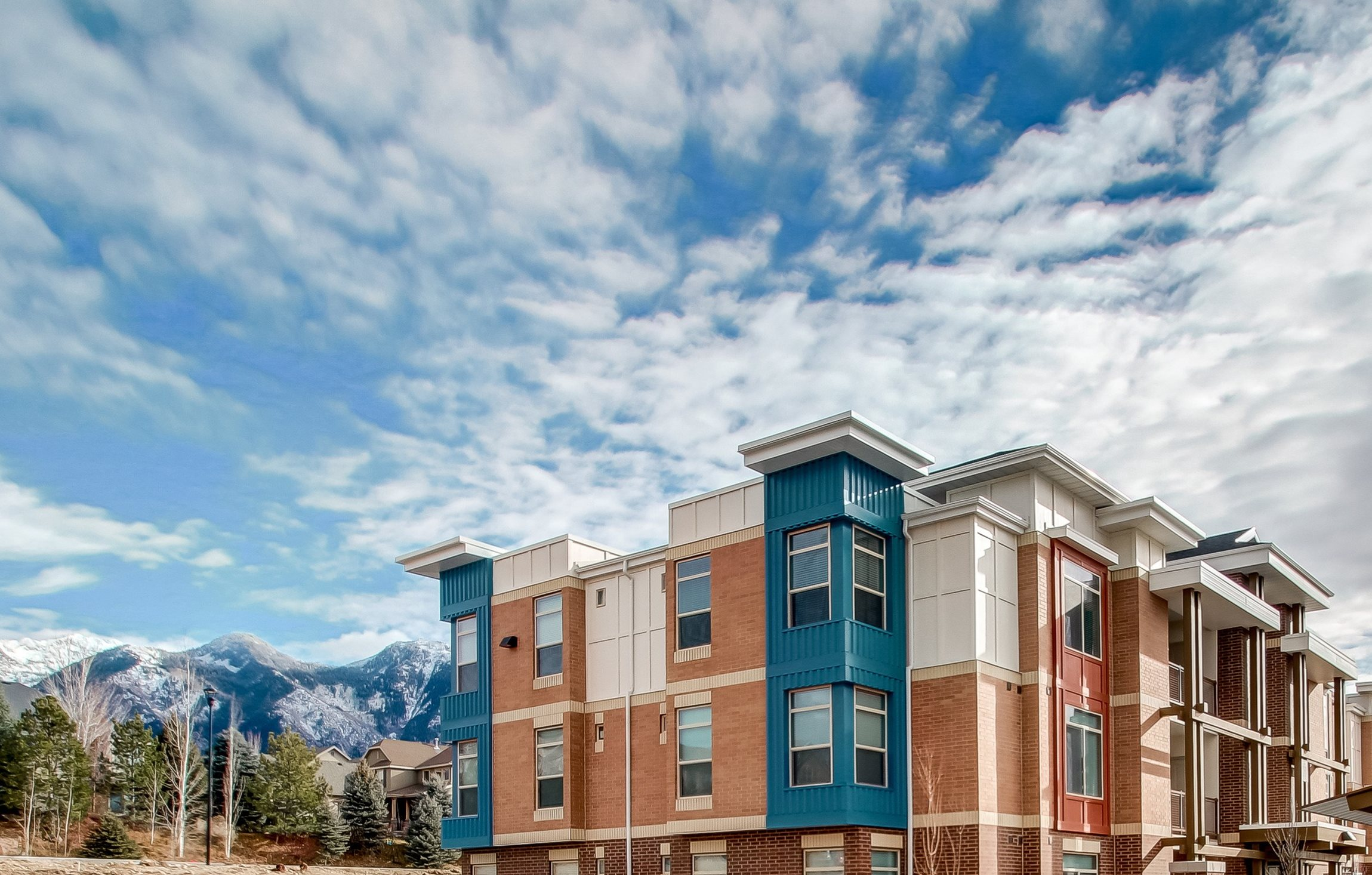 Muti Colored Apartment Building Exterior with Trees Carports and Mountains in the Background