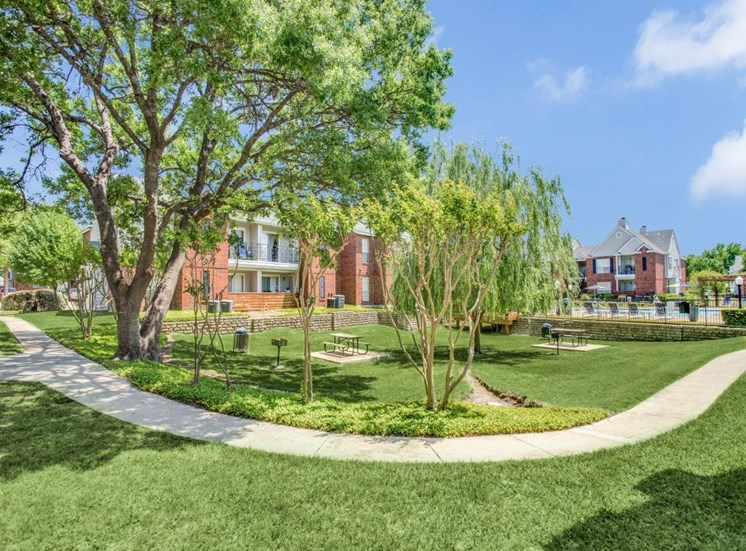 Picnic area with grills next to the apartment buildings and near the enclosed swimming pool