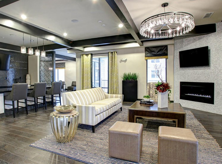 Clubhouse interior with  black crown molding and white ceilings, a chandelier, light gray and white striped sofa, three bar chairs sitting next to the kitchen island, a television mouthed above the fireplace, and hardwood style flooring