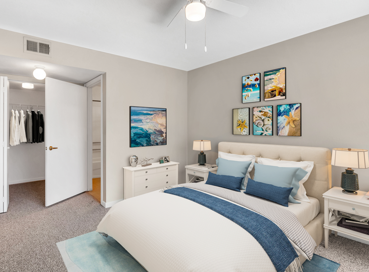 Virtually staged bedroom with wall art, floor rug, night stands, desk lamps, bed, dresser, reach-in closet, and en-suite bathroom