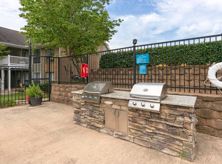 Poolside Summer Kitchen Grilling Stations Against Fence on Retaining Wall