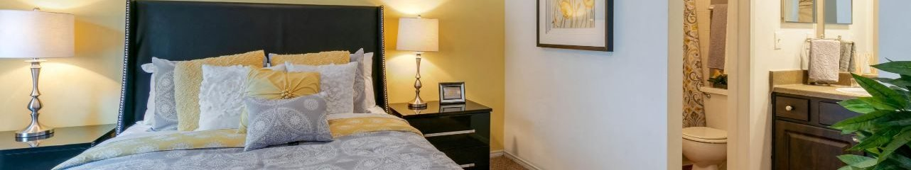 Model Bedroom with En-suite Bathroom Yellow Accent Wall Bed and Nightstands