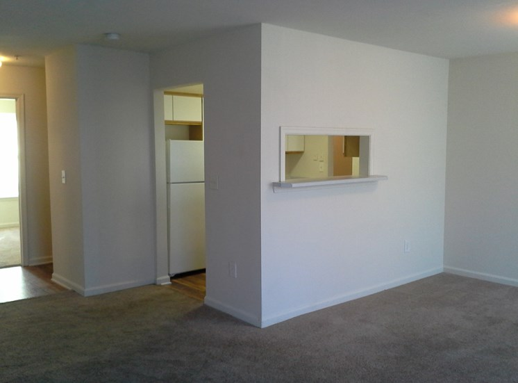 Carpeted Living Room Connected to Breakfast Bar of Kitchen at Columbia Hills Apartments, Tennessee