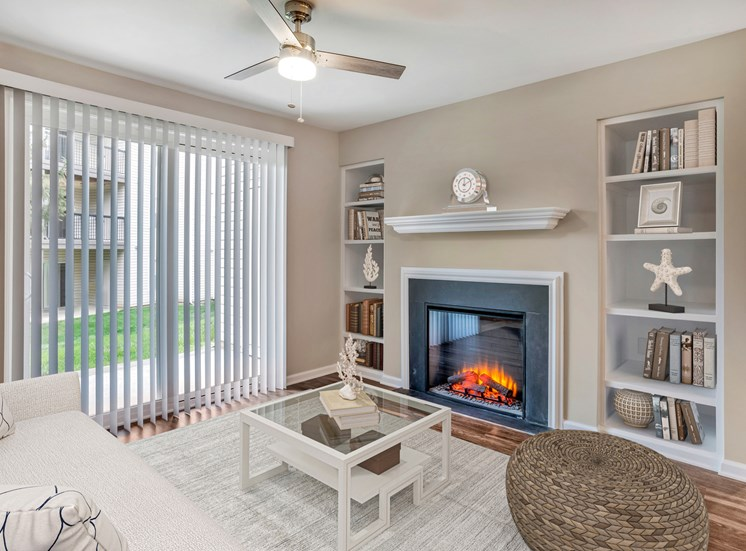 A virtually staged living room with hardwood style flooring, gray walls with white trim, a sliding glass door with vertical blinds, an electric fireplace and built-in shelves on either side of the fireplace.